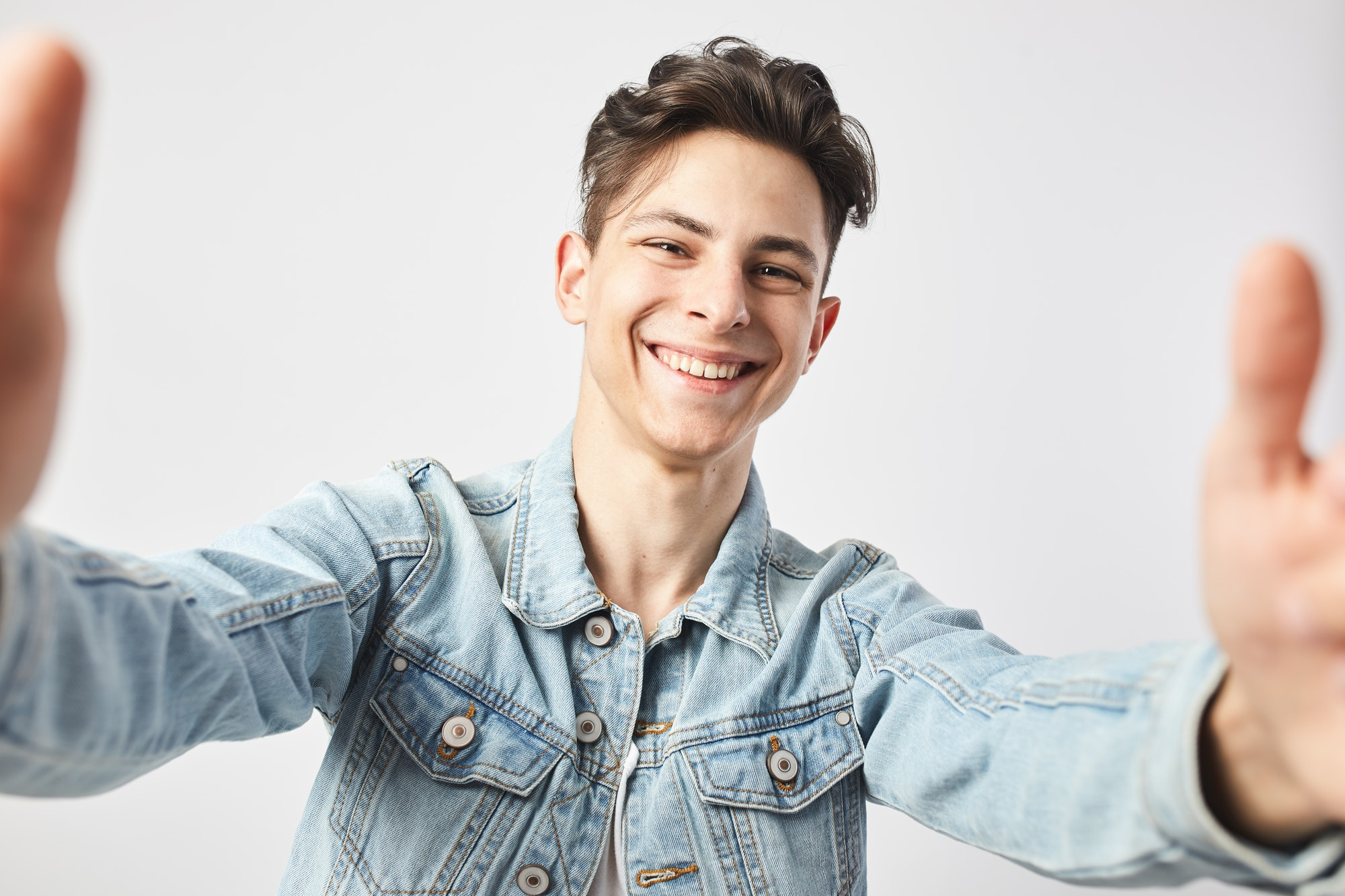 Smiling dark-haired guy dressed in a white t-shirt and a denim jacket makes a salfie on the white