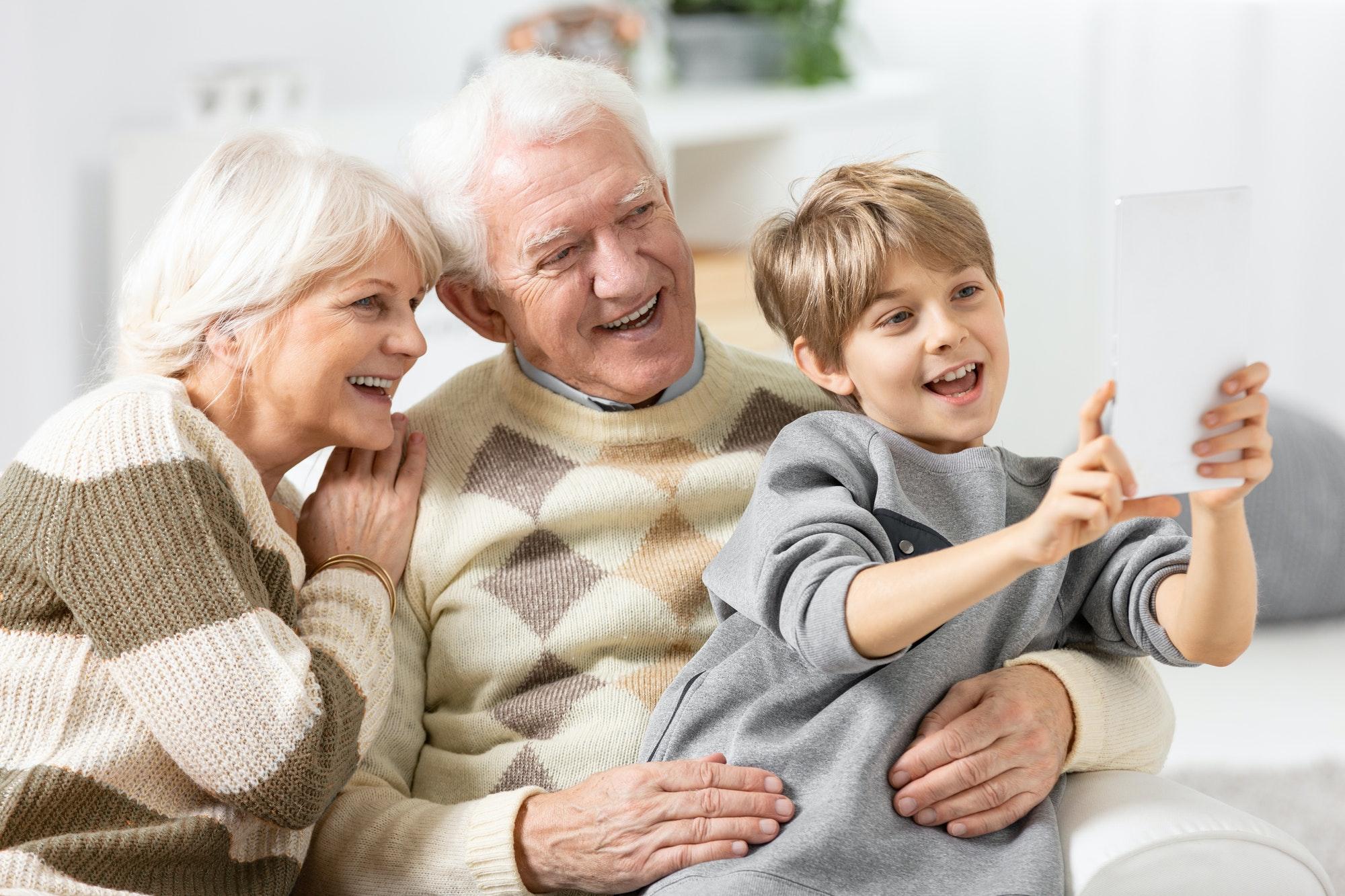 Smiling grandson taking selfie of himself and his happy grandpar